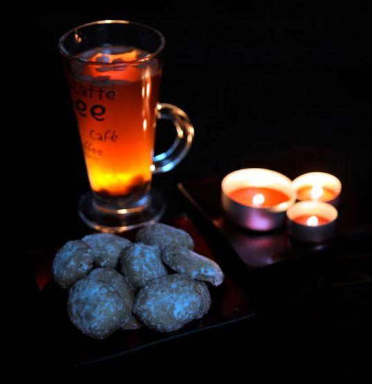 Glögilasi, pikkuleipiä ja kolme palavaa kynttilää