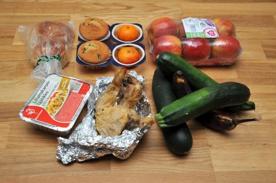 Lattialla kesäkurpitsoita, banaani, broilerinkoipia, lihamakaronilaatikkopaketti, kaksi pullaa, kaksi muffinia, kaksi klementiiniä ja sikspäkki omenoita.