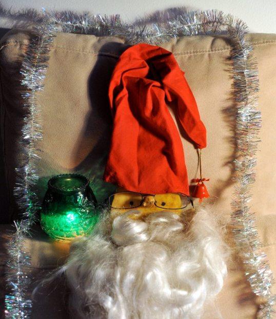 Joulupukin partaan, tonttulakkiin ja silmälaseihin pukeutunut lantunpuolikas palavan kynttilän ja kimallenauhan vierellä.