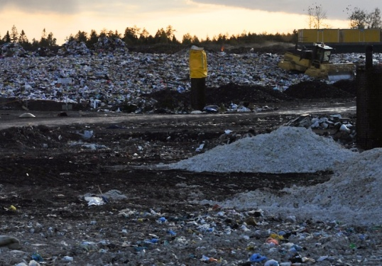Muovikassikasoja ja puskutraktori kaatopaikalla.