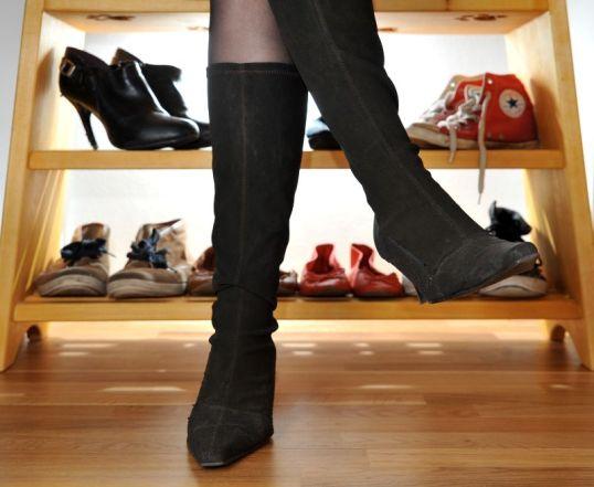 Saappaat naisen jalassa, taustalla erilaisia kengiä telineessä.