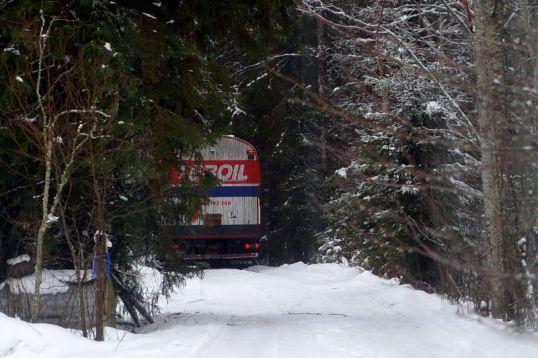 Öljysäiliön luota loittoneva säiliöauto näyttää häviävän metsän sisään.
