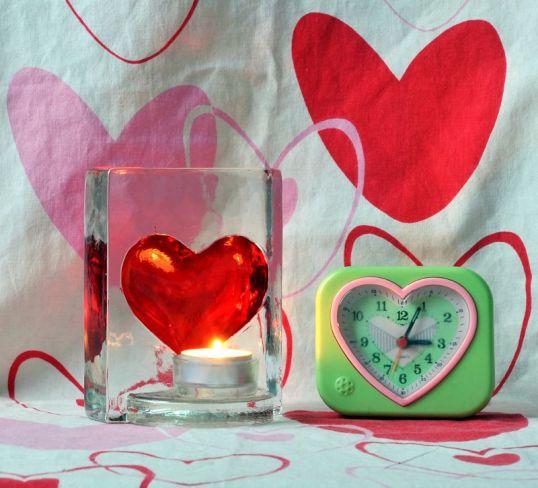 Kynttilälyhty, jossa punainen sydän, ja herätyskello, jossa sydämen muotoinen kellotaulu. Taustalla sydämillä kuvioitu pussilakana.