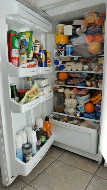 Avoin jääkaappi, jonka hyllyt pursuilevat erilaisia elintarvikkeita.