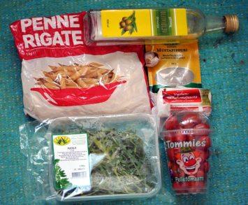 Pennepastapussi, rucolapakkaus, tomaattipurkki, vuohenjuustopaketti, mustapippuripussi, oliiviöljypullo ja valkosipulia matolla.
