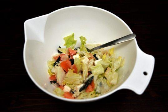 Valkoisessa kulhossa jäävuorisalaattia, salaattijuustoa, tomaattia ja jotain muuta.