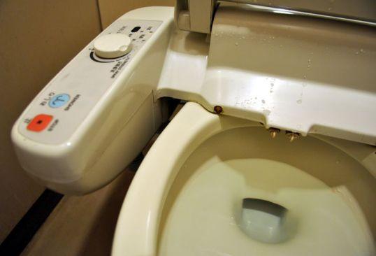 Japanilainen WC-istuin, jossa on kiinni puhdistussuihkun ohjausyksikkö.