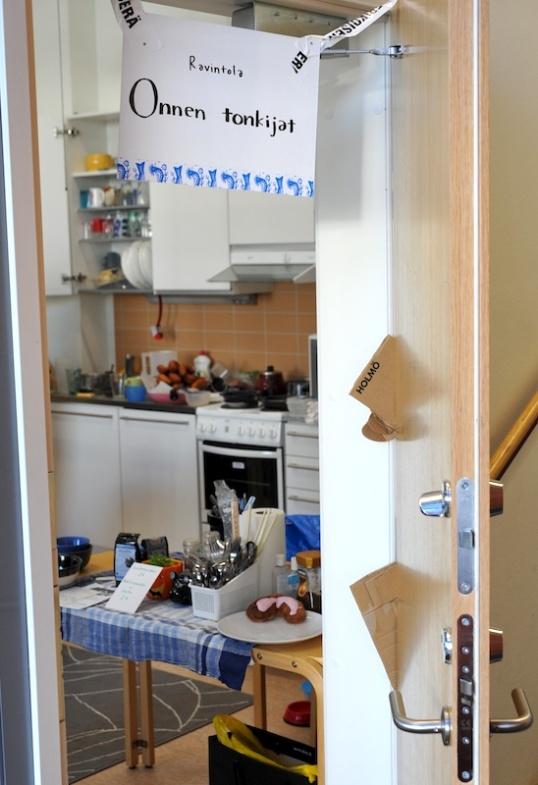 Ovi auki tilaan, jossa näkyy keittiö ja ruokailuun liittyvää välineistöä.