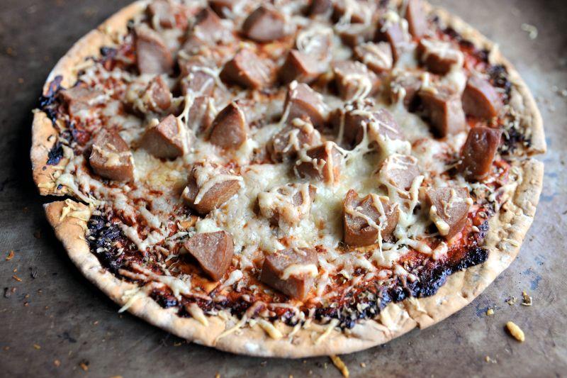 Pyöreä pitsa, jonka päällä makkaraa, tomaattikastiketta ja juustoa.