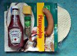 Valmis pitsapohja, ketsuppipakkaus, oreganopurkki, juustonpala ja uunilenkki.