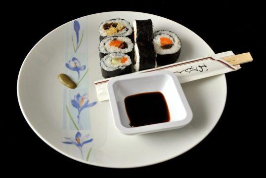 Makeja (täytteinä porkkanaa, kurkkua, herkkusieniä ja munakasta), syömäpuikot, wasabia ja kuppi soijakastiketta lautasella.