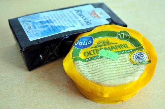 Pakkaus Oltermanni-juustoa venäläisin tekstein ja paketti Russia-nimistä teetä.
