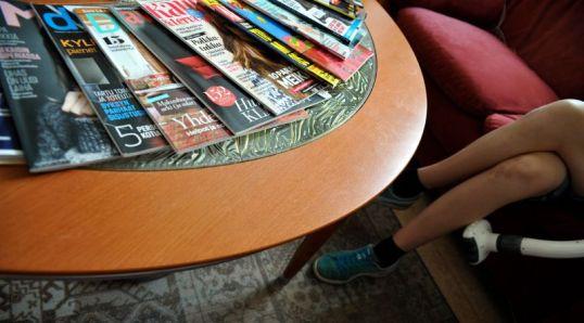 Aikakauslehtiä pöydällä ja hieromalaite jalalla.