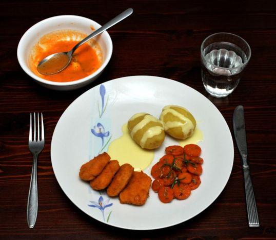 Pöydällä keittolautanen ja ruokalautanen, jolla perunoita, broilerinugetteja, porkkanoita ja keltaista kastiketta.