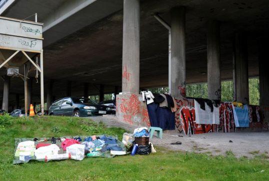 Nurmikolla vaatteita pressun päällä, sillan alla vaatteita suihkuverhojen päällä, graffitien lomassa.