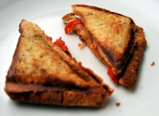 Päällekkäiset ja puolitetut paahtoleivät, joiden sisällä juustoa ja paprikaa.
