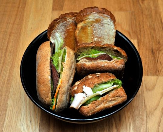 Lautasella voideltuja paahtoleipiä sekä juustolla, leikkeleillä, kurkulla ja salaatilla täytettyjä sämpylöitä.