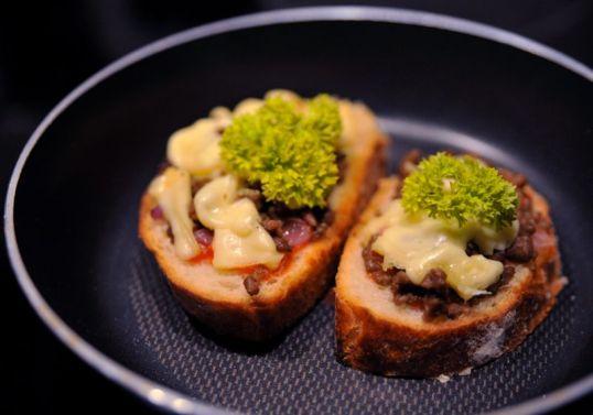 Paistinpannulla leipäviipaleita, joiden päällä juustoa, jauhelihaa, punasipulia, ketsuppia ja persiljaa.