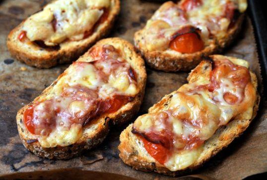 Uunipellillä sekaleipäviipaleita. joiden päällä juustoa, serranonkinkkua ja tomaattia.