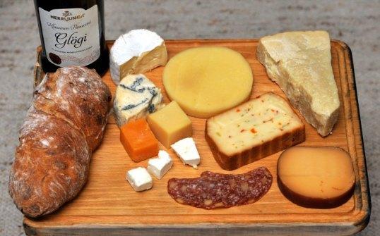 Puisella tarjottimella glögipullo, leipä, leikkeitä ja monenlaisia juustoja.