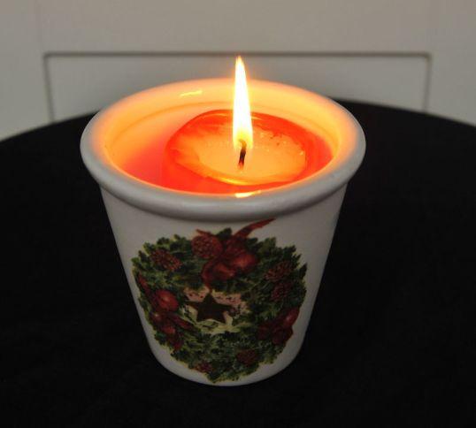 Punainen kynttilä palaa kupissa, jossa on jouluaiheinen koristepainatus.