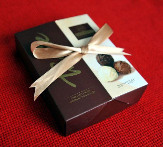 Rusetilla solmittu suklaarasia punaisella kankaalla.