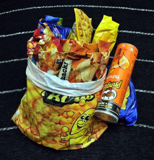 Puolityhjiä sipsipusseja ahdettuna juustonaksujen mainoskassiin. Vieressä perunalastuputkilo.