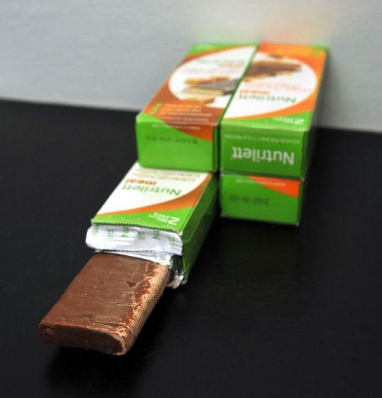 Neljä pakettia ateriankorvikepatukoita. Yksi suklaapäällysteinen patukka osittain kääreistä kuorittuna.