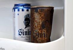 Ruostunut oluttölkki ja vastaava alumiinitölkki jääkaapin ovessa.