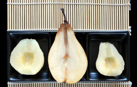 Säilykepäärynän puolikkaita ja tuoreen päärynän puolikas mustalla lautasella.