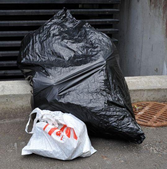 Täysi jätesäkki asvaltilla pienen muovipussin vieressä.