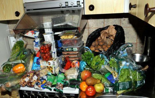 Iso kasa elintarvikkeita keittiössä lieden ja tiskipöydän päällä.