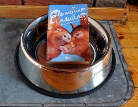 Eläimellinen nautinto -kirja lattialla koiran isossa ruokakupissa.