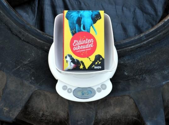 Eläinten oikeudet -kirja vaakakupissa digitaalisen vaa'an päällä, joka on päällä ja lukemassa 540 traktorin renkaan päällä.