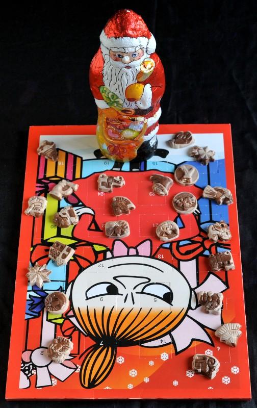 Pikku Myy -suklaakalenterin päällä kalenterin harmaantuneita suklaita sekä suklaapukki kääreissään.