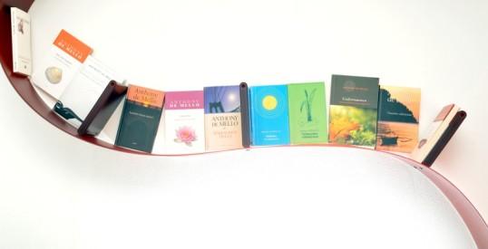 Anthony de Mellon suomenkieliset teokset rivissä punaisessa Bookworm-kirjahyllyssä.