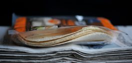 Tortilloja avatussa pakkauksessa sanomalehtipinon päällä.