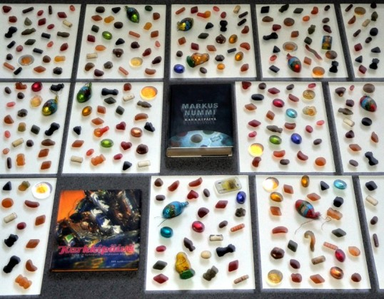 Karamelleja ja suklaita vierekkäisten A4-arkkien päällä sekä kaksi Karkkipäivä-kirjaa.