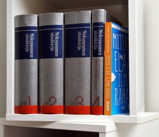 Neliosainen Nykysuomen sanakirja ja Miten elää ilman rahaa neliön muotoisessa hyllyssä.