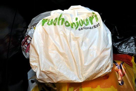 Ruohonjuuren valkoinen muovikassi sekajäteastiassa muiden muovikassien päällä.