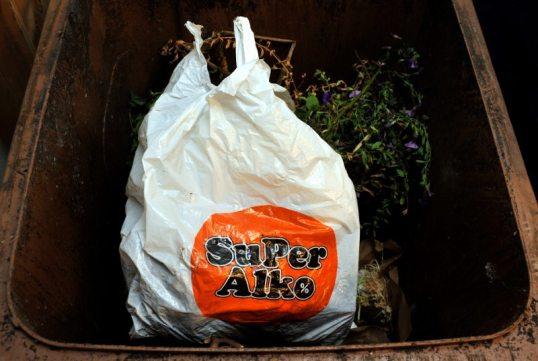 Superalkon valkoinen muovikassi biojäteastiassa kasvien seassa.