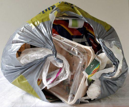 Aukinainen roskapussi, josta pursuaa muovirasia ja muuta roskaa.