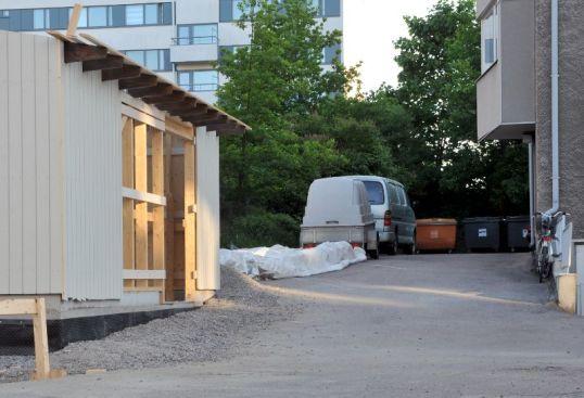 Rakenteilla oleva jätekatos, josta puuttuu ovi. Taustalla jäteastioita.