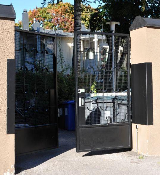 Metallinen portti sulkeutumassa. Taustalla jäteastioita.