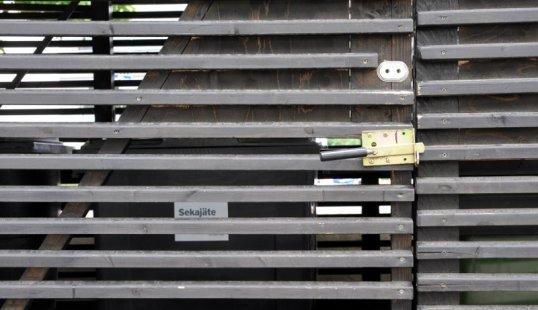 Jätekatoksen ovi, jossa sekä kahvallinen salpa että kaksoispesällinen lukko. Taustalla sekajäteastia.