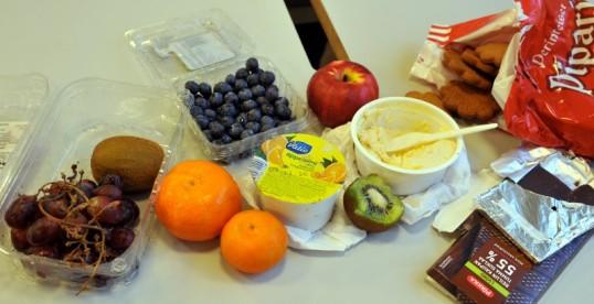 Pöydällä viinirypäleitä, kiivejä, klementiinejä, pensasmustikoita, appelsiinimehupurkki, omena, rahkaherkkua, tummaa suklaata ja pipareita.