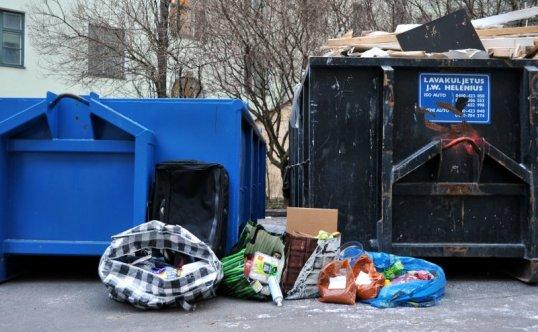Kahden jätelavan edessä muovisia kestokasseja, joista pursuaa ruokapakkauksia.