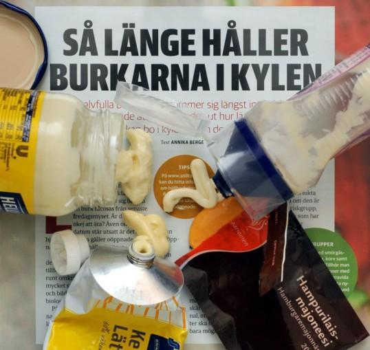 Lehtiartikkelin päällä lasipurkista, muovisesta pursotinpurkista, muovipussukasta ja metalliputkilosta ulos tullutta majoneesia.