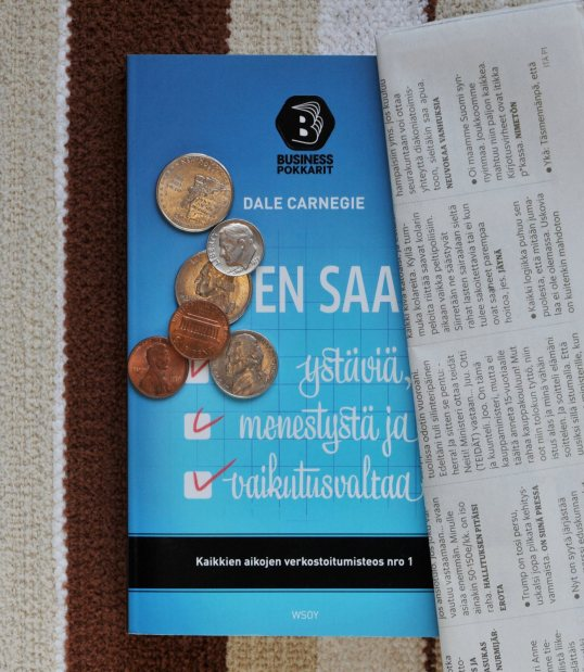 Miten saan ystäviä, menestystä ja vaikutusvaltaa -kirjan päällä yhdysvaltalaisia kolikoita ja HS Metro -lehden tekstiviestipalstaa.