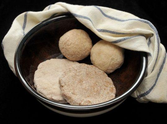 Kaksi sämpylää ja kaksi ohutta leipää Kermansaven kulhossa, jonka ympärillä on siniraidallinen liina.